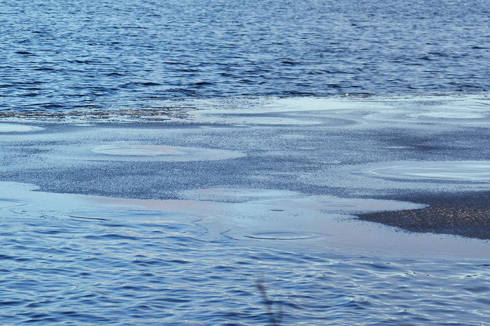 Lähikuvaa järven pinnasta, jonka peittää osittain ohut jääkerros.